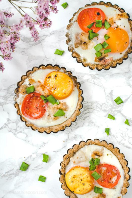 Tartaletki orkiszowe z jajkiem i boczkiem Ilość: 6 tartaletek Składniki na ciasto: 200 g mąki orkiszowej 1 jajko 100 g zimnego masła Szczypta soli Składniki na nadzienie: 6 małych jaj 1 kulka mozzarelli 100 g boczku pokrojonego w kostkę 3-4 pomidorki koktajlowe szczypiorek sól i pieprz Zimne masło kroimy w kostkę i dodajemy do mąki i jajka. Rozdrabniamy na kruszonkę, a następnie wyrabiamy ręką. Jeżeli ciasto będzie za suche, dodajemy 1 łyżkę lodowatej wody. Zawijamy w folię i wstawiamy do lodówki na 30 minut. Formy do tartaletek smarujemy masłem i nagrzewamy piekarnik do 190 stopni. Dzielimy ciasto na 6 porcji, każdą wałkujemy w okrąg i wylepiamy nią foremki. Pieczemy 10 minut. W tym czasie podsmażamy boczek, mozzarellę i pomidorki kroimy w plasterki. Na spodzie upieczonych tartaletek układamy po plasterku sera. Wbijamy do każdej jedno jajko (w miarę potrzeby odlewamy trochę białka, jeżeli jaja są za duże), układamy boczek i plasterki pomidorów. Pieczemy 10-15 minut, aż białko się zetnie. Podajemy posypane szczypiorkiem.